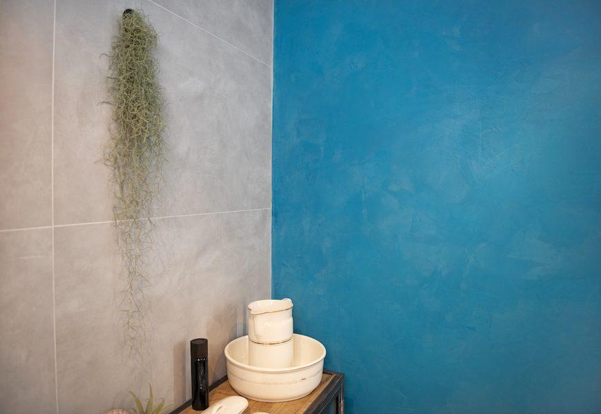 De blauwe wand is een kleurrijk element naast de grote grijsbeige tegels.